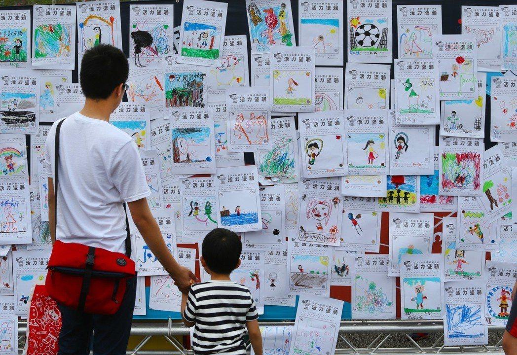 在一個兒童節的活動上,一名小朋友將自己的圖畫紙貼在塗鴉牆上,展現活力塗鴉。這個一...