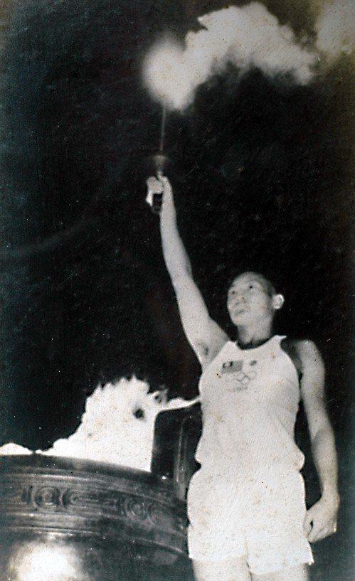 1964年東京奧運當年台北傳遞聖火的林竹茂在市立體育館點燃聖火的歷史照片。記者林...