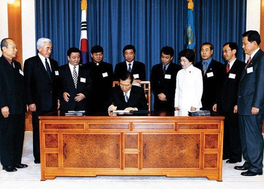 2000年11月,金大中(圖中)總統簽字的〈濟州四三事件真相調查及恢復遇難者名譽...