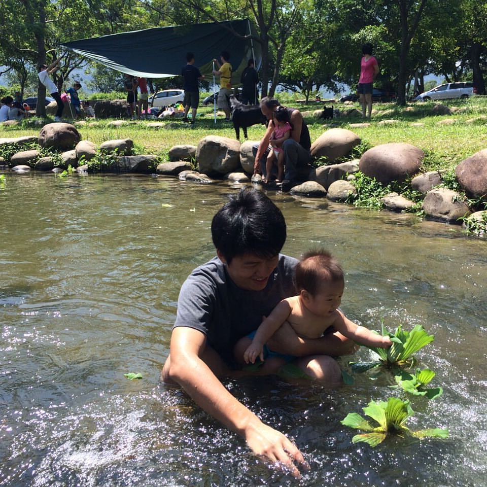 龍潭三坑自然生態公園戲水渠道旁有草原,鋪上野餐墊就能在這裡度過一下午。圖/讀者陳...