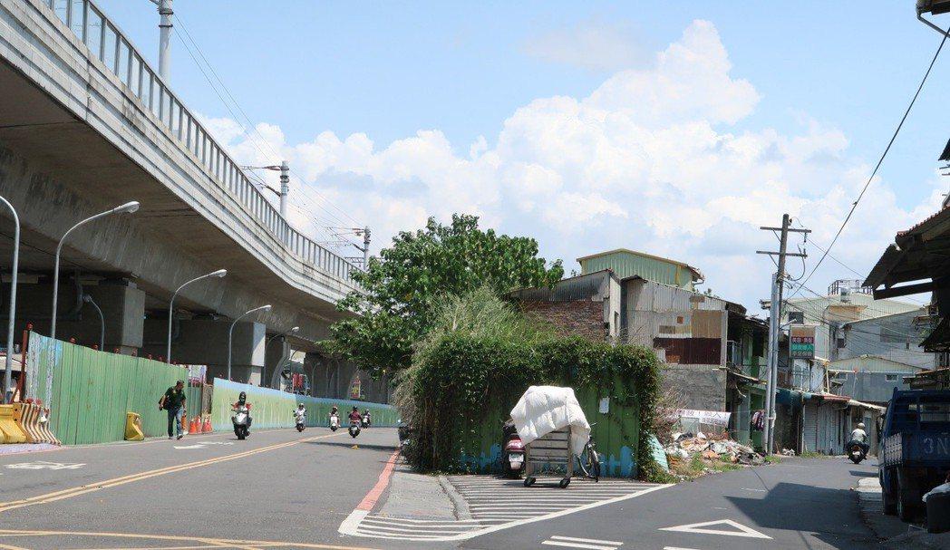 屏東市後火車站前的公勇路拆除工程已暫緩,但仍可見住戶懸掛的不滿布條。記者翁禎霞/...