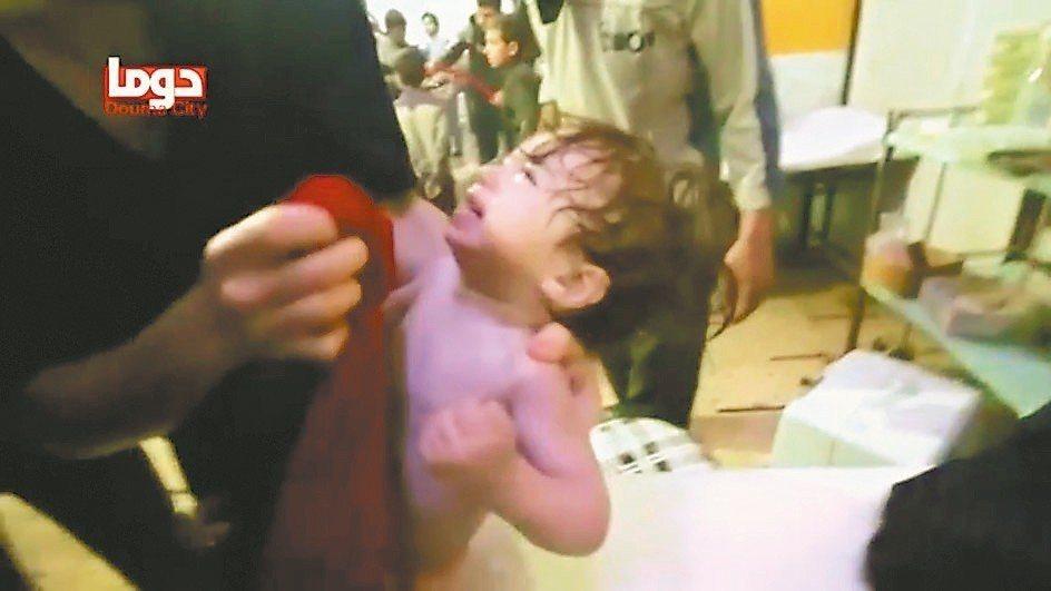 敘利亞醫護人員安撫一名遭毒氣攻擊嚇哭的孩童。 (路透)