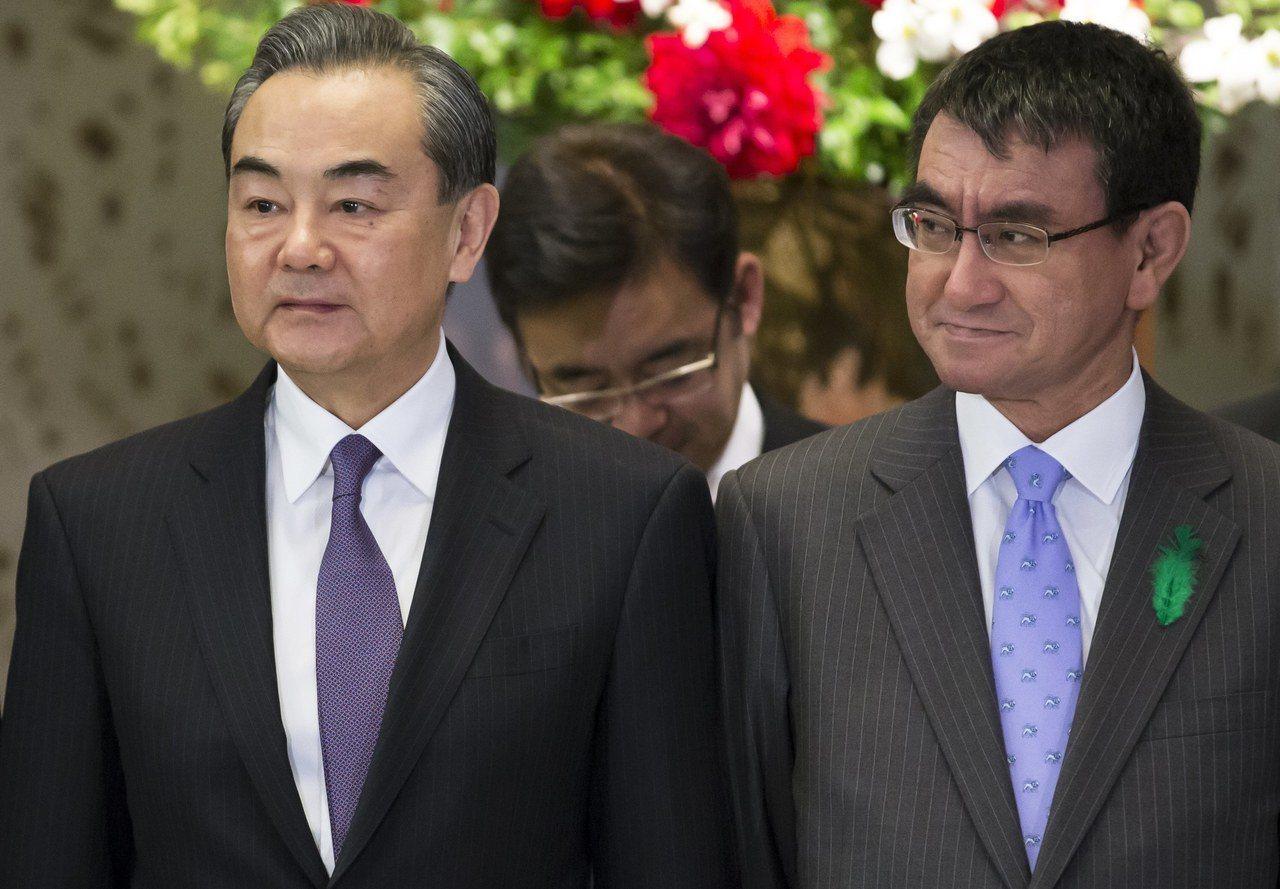 日本外相河野太郎(圖右)和中國外交部長王毅(圖左)16日在東京舉行經濟高層對話前...