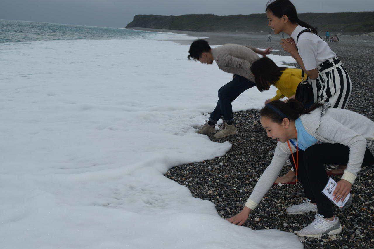 這群來自蒙古的孩子,紛紛脫下鞋襪,期待感受海水碰觸雙腳的感覺。圖/世界展望會提供