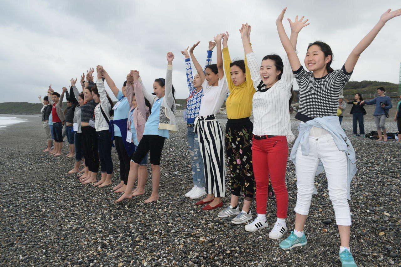 來自蒙古的孩子看見七星潭海水,看到湛藍的海洋無不雀躍開心,高舉雙輩。圖/世界展望...