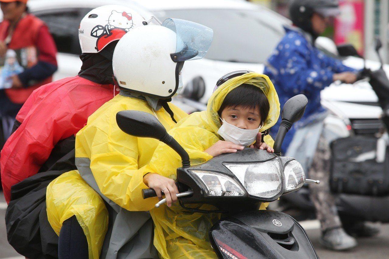 民眾外出穿戴雨具。記者楊萬雲/攝影