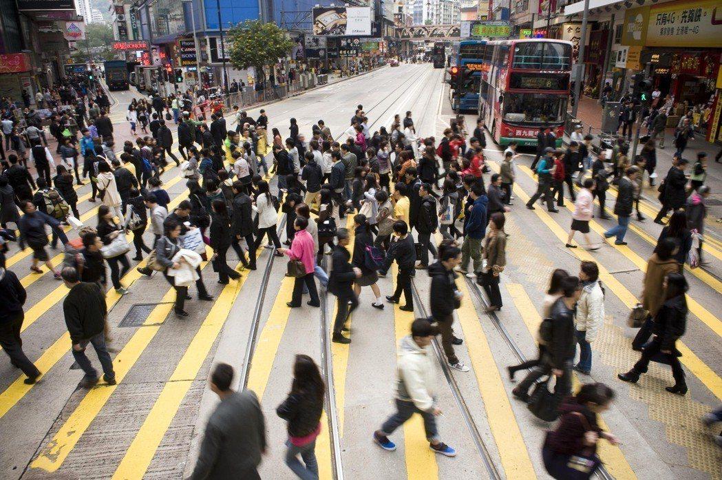 行人走過香港銅鑼灣鬧市區的馬路。新華社
