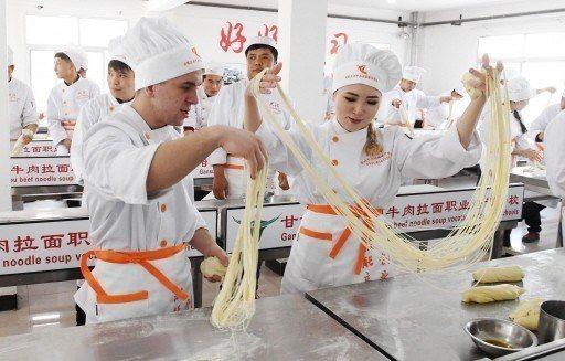 來自哈薩克、澳大利亞等國學員在甘肅興隴蘭州牛肉拉面職業培訓學校學習牛肉麵製作工藝...