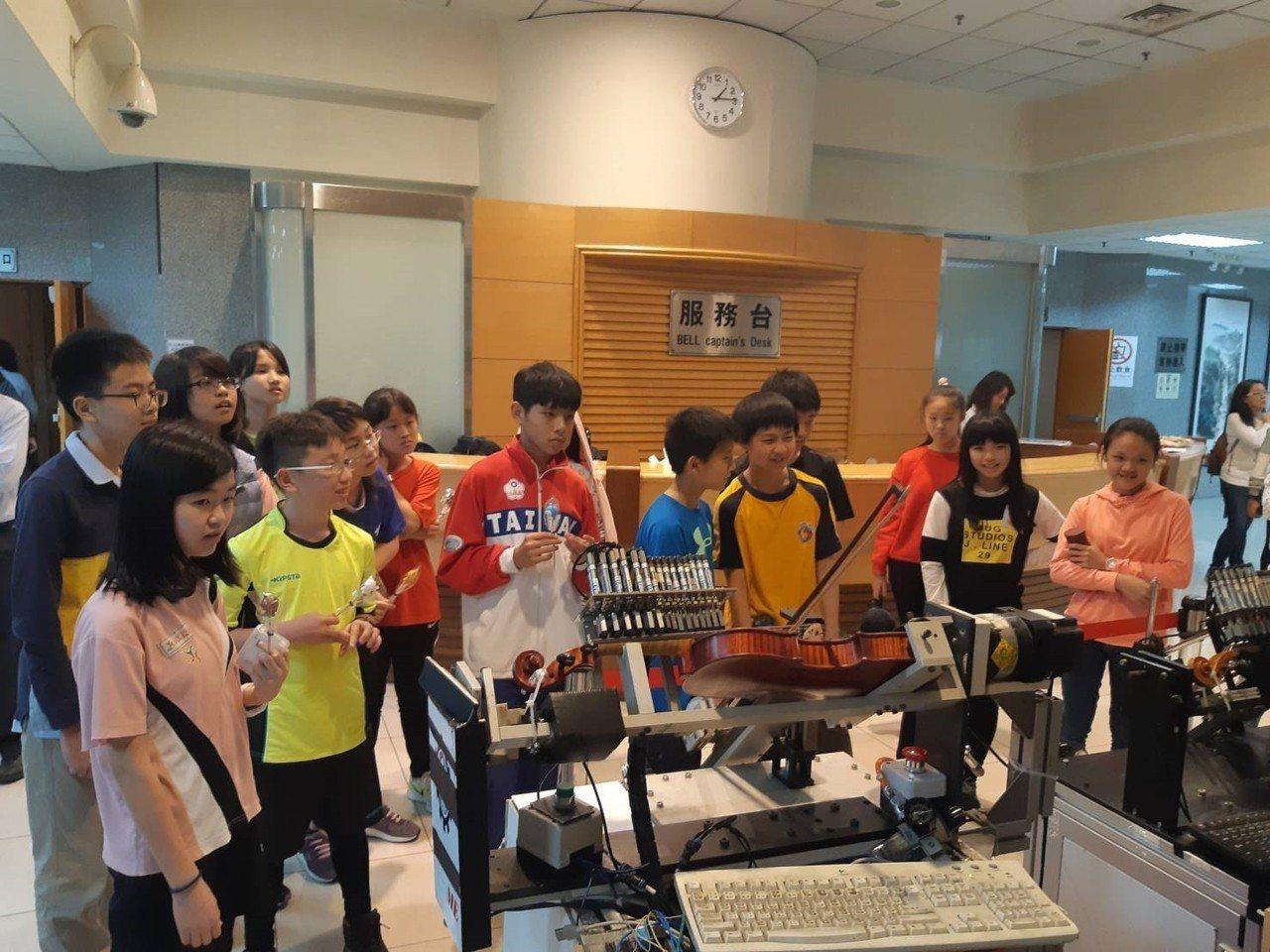 學童們好奇看著機車如何演奏提琴。圖/中原大學提供
