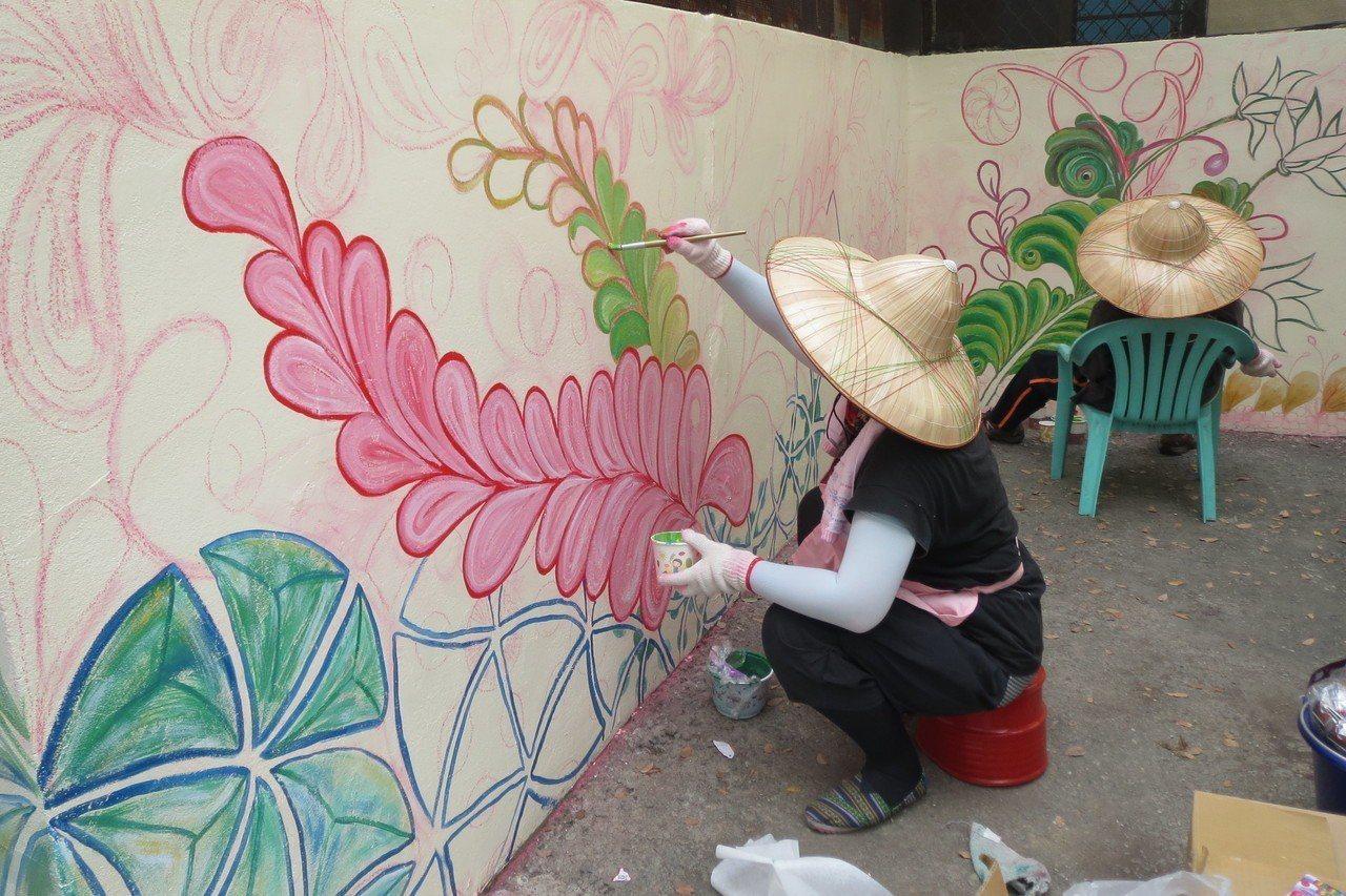 梓平社區的家庭主婦們天天站在牆壁前,揮著汗穿梭在顏料罐間彩繪。圖/高雄市農業局提...