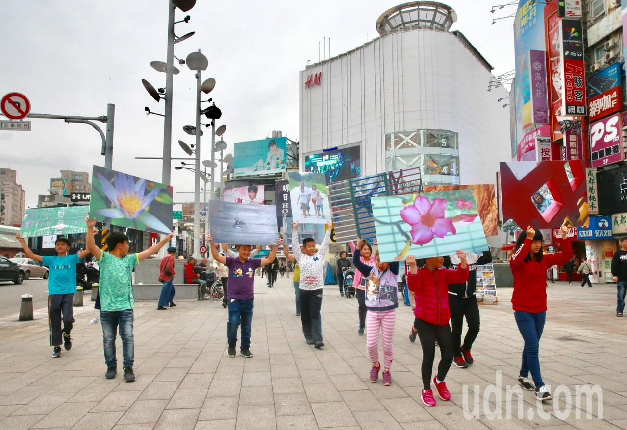 來自高雄後山正新庄國小的十多位學童,下午在西門町進行「快閃街頭攝影展」。記者黃義...
