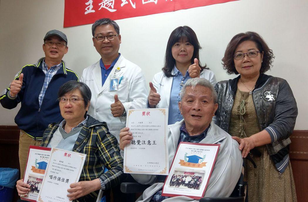 蔡秀盡(前排左)、王桂崇(前排右)開心展示主題式團體治療課程結業證書,以及唱作俱...