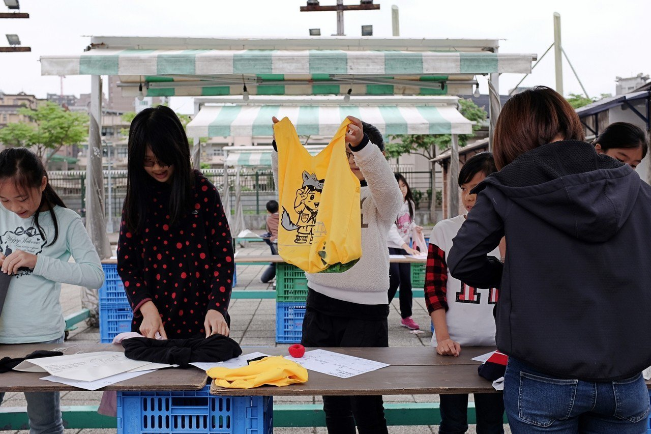 國小學童與綠色環保單位代表,共同體驗舊衣T恤改造環保袋DIY 。記者沈佩臻/攝影