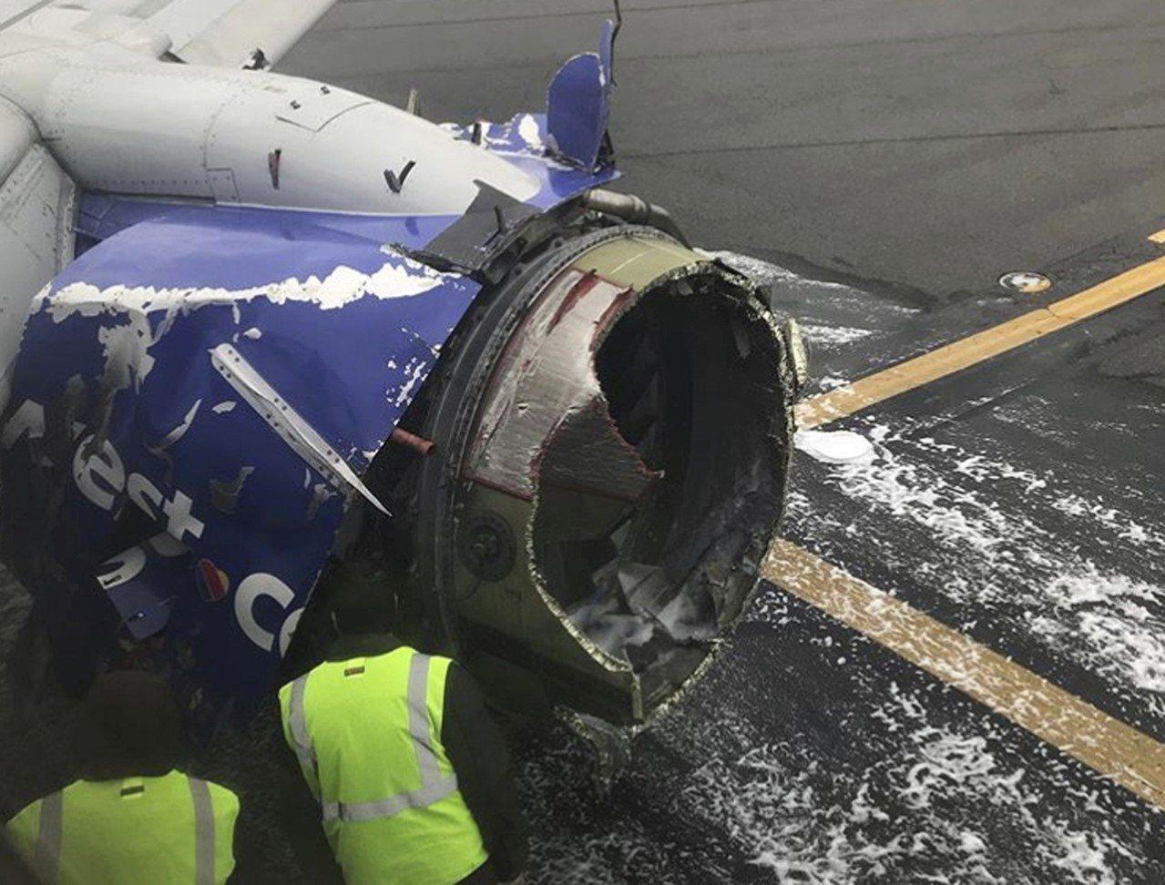 圖為工程師在檢查美國西南航空1380飛機左側引擎。 美聯社