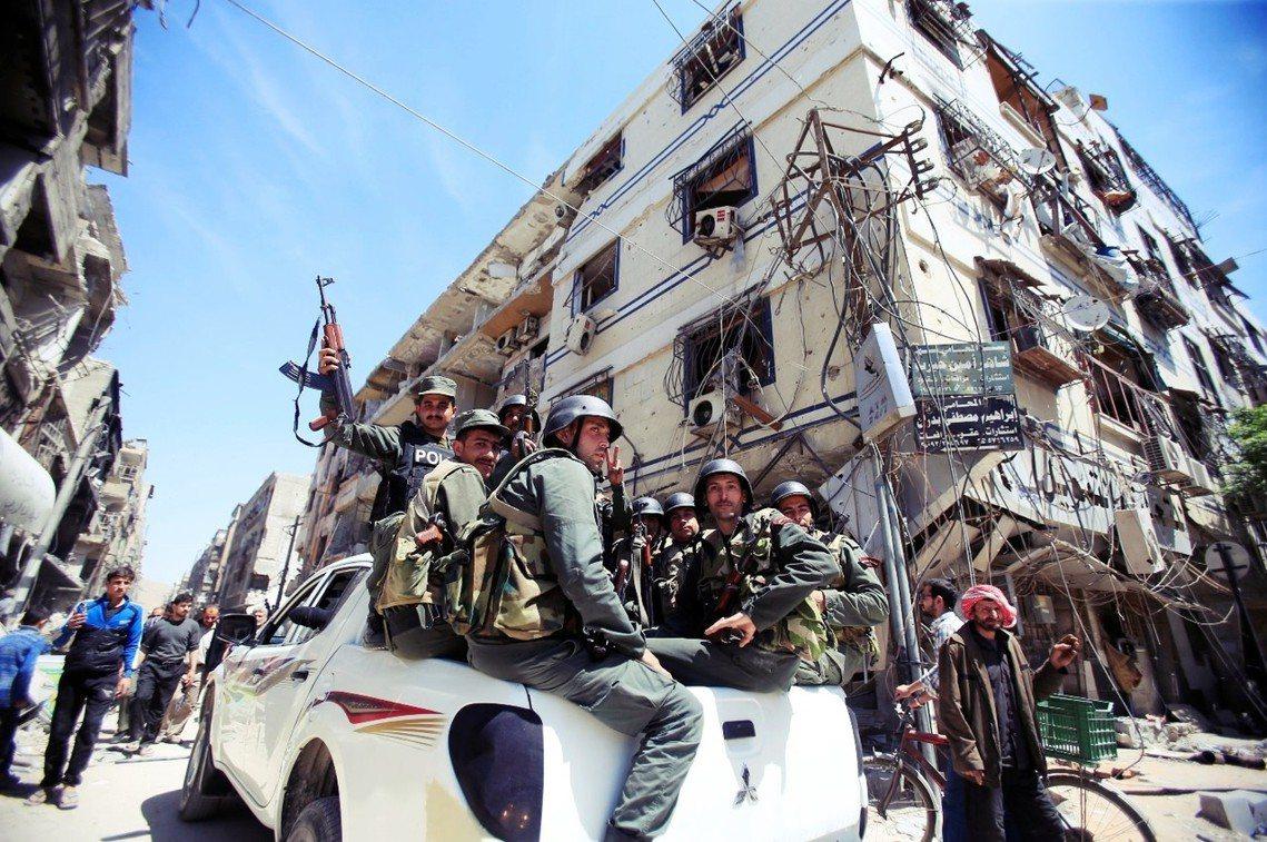 收復東烏塔地區後,阿薩德政府警隊在杜馬鎮巡邏。 圖/路透社
