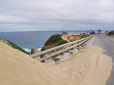 公路局在墾管處成立前規劃興建的佳鵝公路,未經環評專家審慎評估,不僅阻斷沙源流動,造成整體景觀缺陷,路上也常有積沙。 記者潘欣中/翻攝