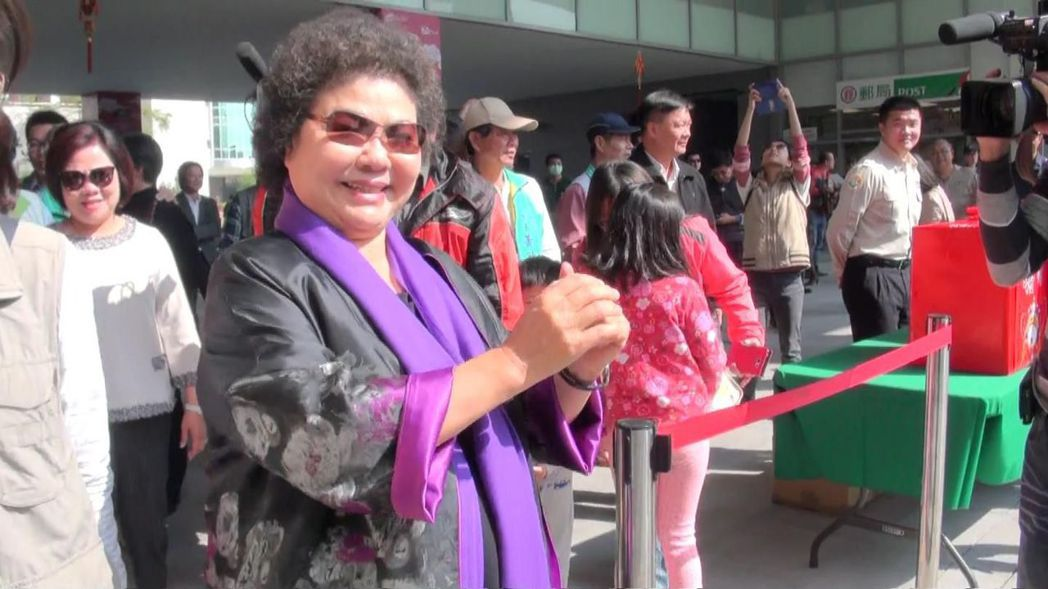 過年發小紅包,陳菊曾用亮紫色圍長圍巾配充滿年節喜氣的外套。 圖/聯合報系資料...