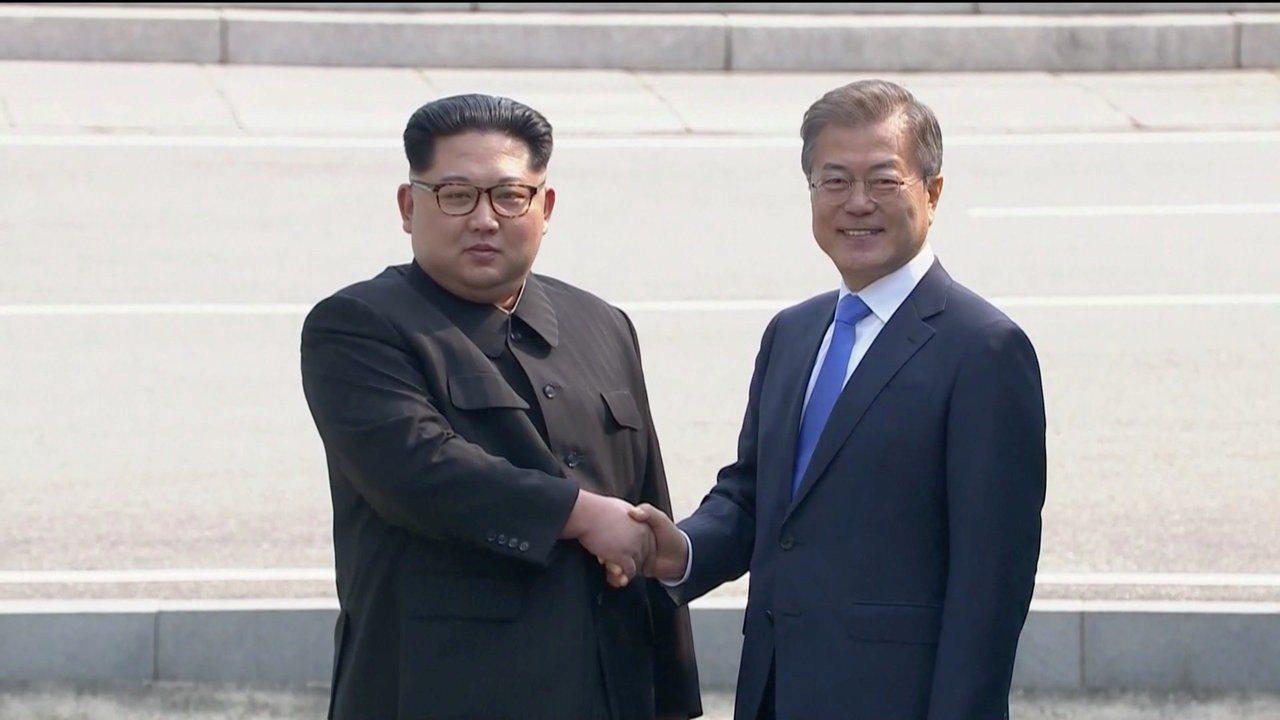 北韓領導人金正恩(左)和南韓總統文在寅世紀握手,兩人面帶微笑。 路透社