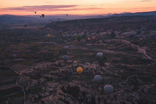 陸續升空的熱氣球,此時大地隱約映著日出前的紅光。 圖/背包客棧