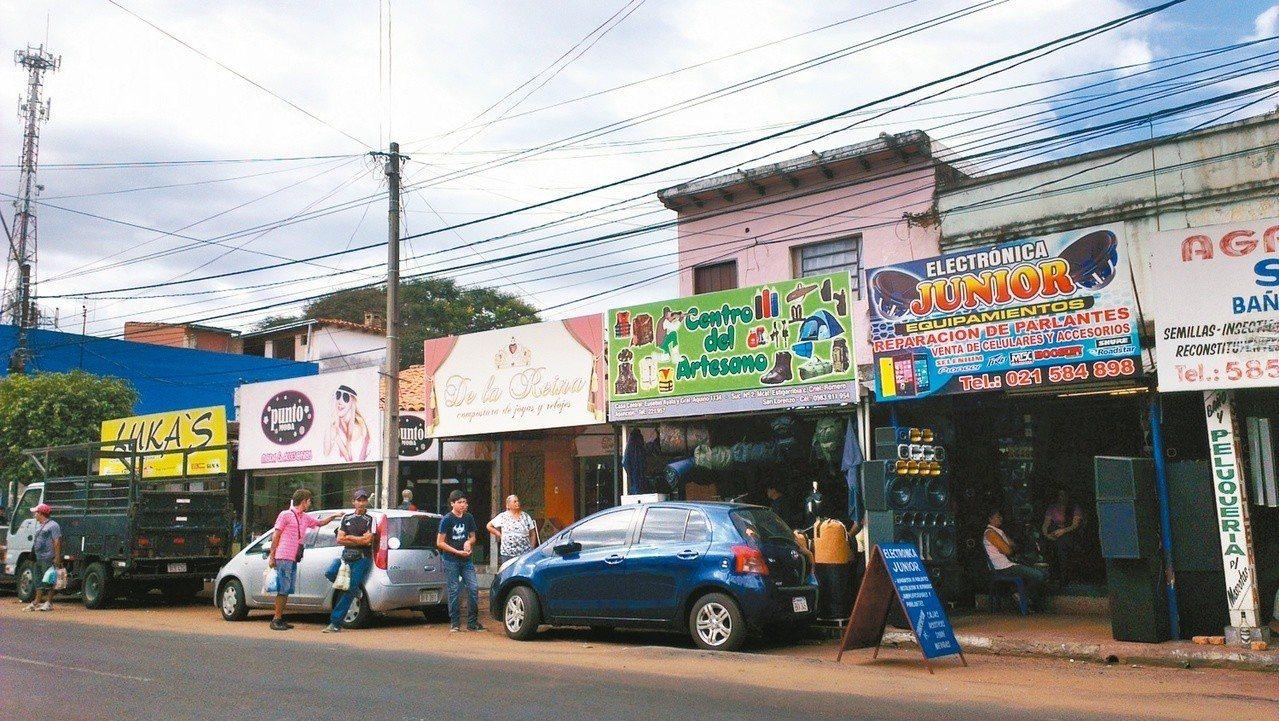 路旁拎著袋子的男人們正準備跳上公車,兜售各式商品。圖/周育如