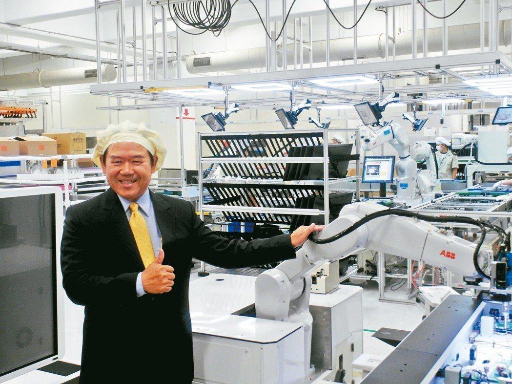 佳世達董事長陳其宏展示佳世達結合行動機器手臂的智慧工廠解決方案。 記者何佩儒/攝...