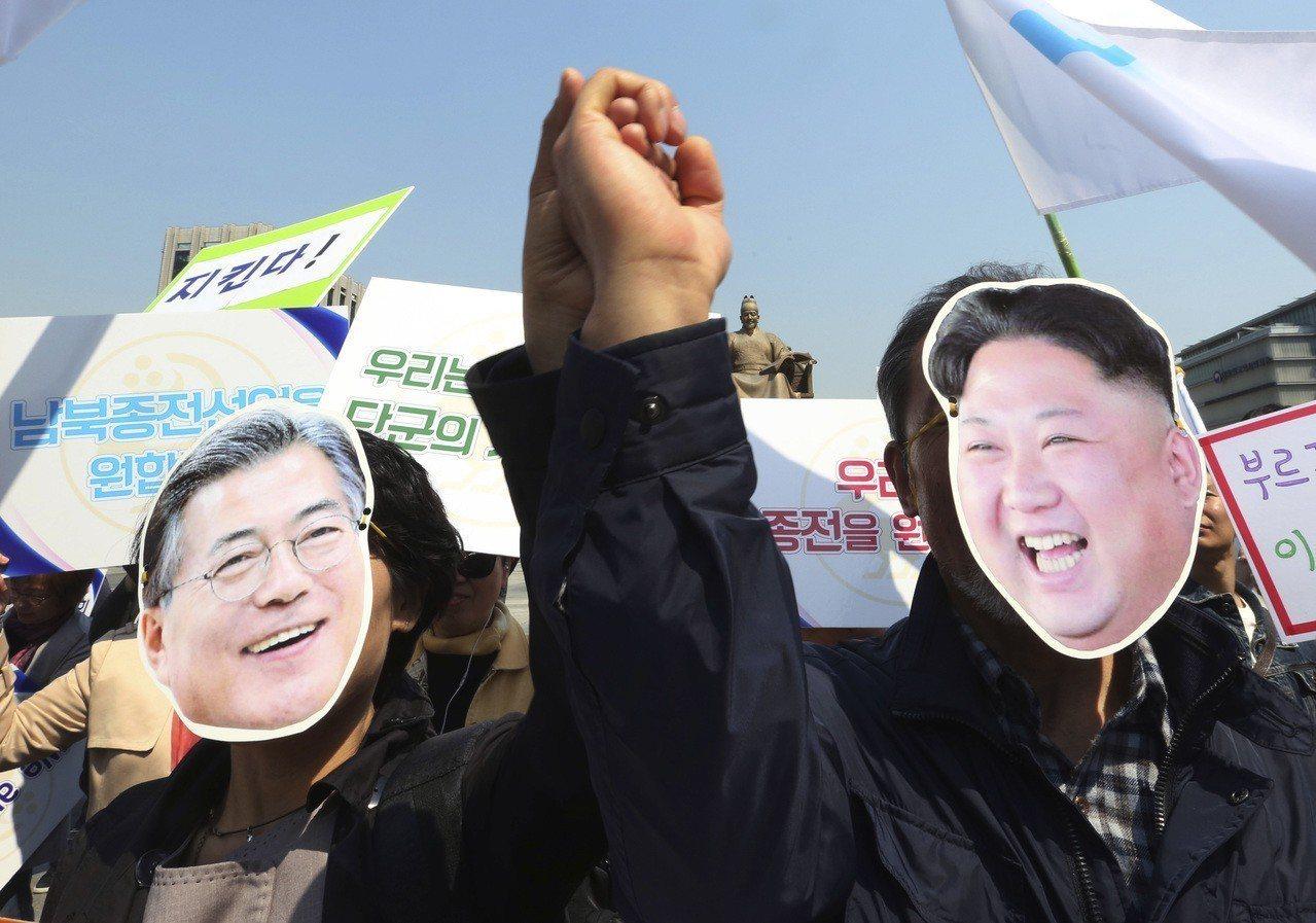 南韓首都首爾25日舉行歡迎兩韓峰會到來的集會,戴著南韓總統文在寅與北韓國家領導金...