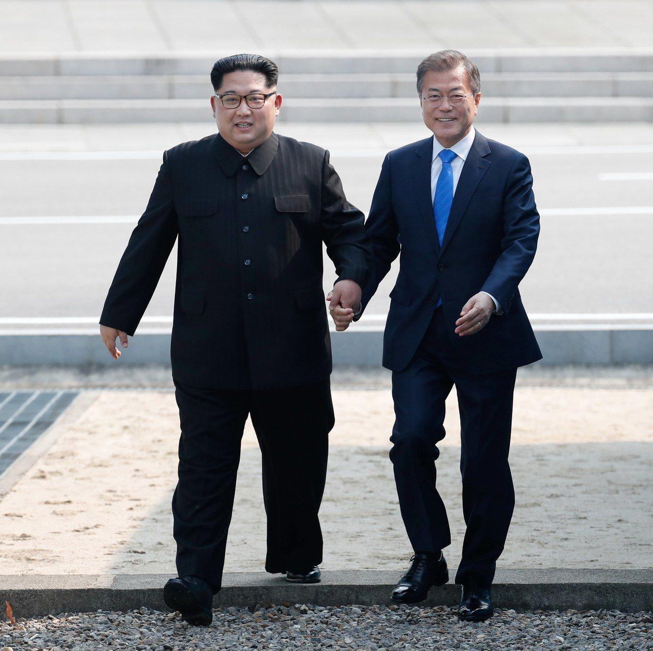兩韓領袖文在寅(右)及金正恩27日牽手跨越軍事分界線。 歐新社