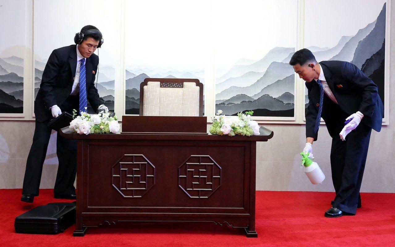 北韓安全官員在金正恩今天早上使用桌子簽留言簿前,先消毒並檢查桌子。 路透
