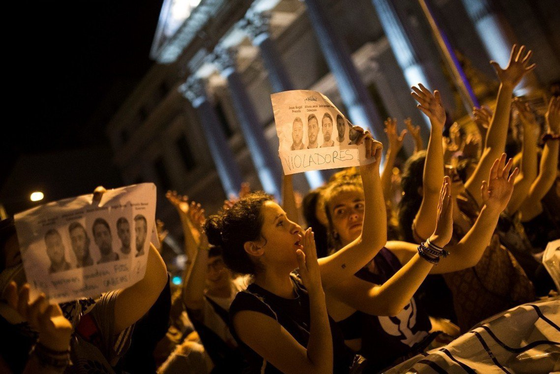 西班牙國會前,抗爭者高舉著五名被告的檔案照,寫下「強暴犯們」。 圖/美聯社