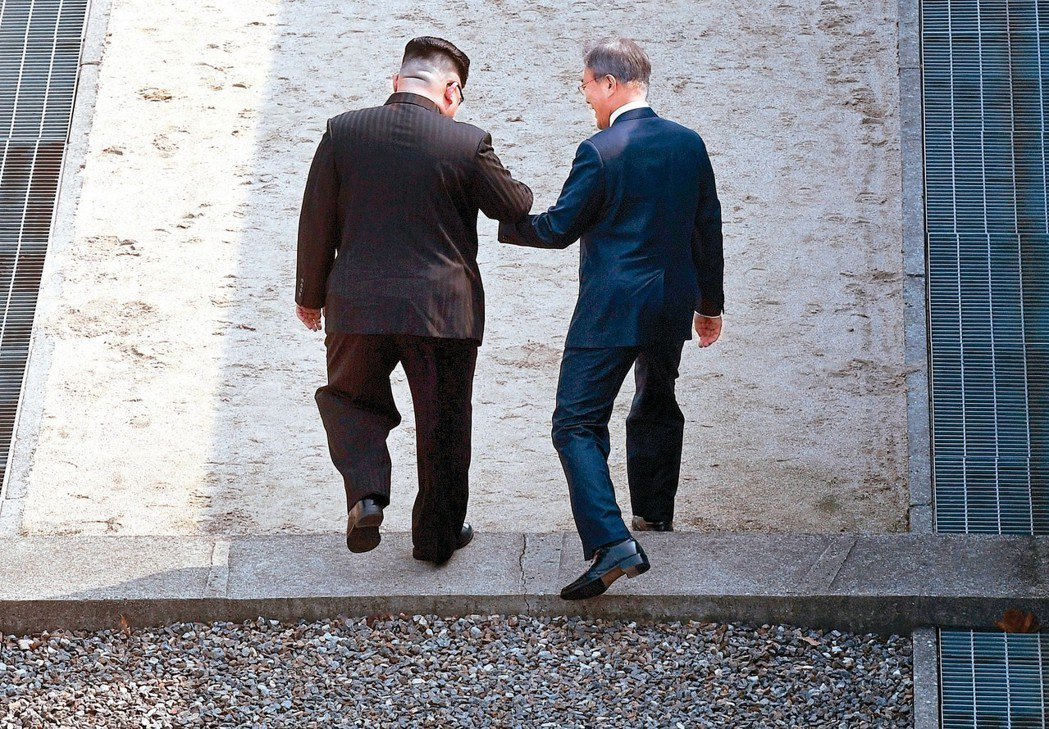 這一跨…迎新頁 北韓領導人金正恩(左)廿七日在板門店即興邀請南韓總統文在寅(右)...