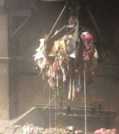焚化廠人員將毒品以抓鉤投入焚化爐銷毀。 記者袁志豪/翻攝