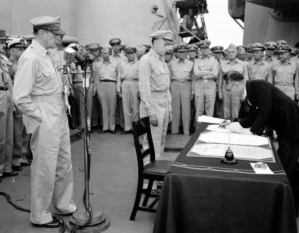 1945年,日本外相重光葵(右)在密蘇里艦上簽署降書,而左邊站立者為麥克阿瑟將軍...