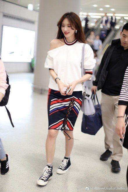 林志玲日前在上海機場穿TOMMY X GIGI聯名系列白色上衣配彩色條紋短裙,以...