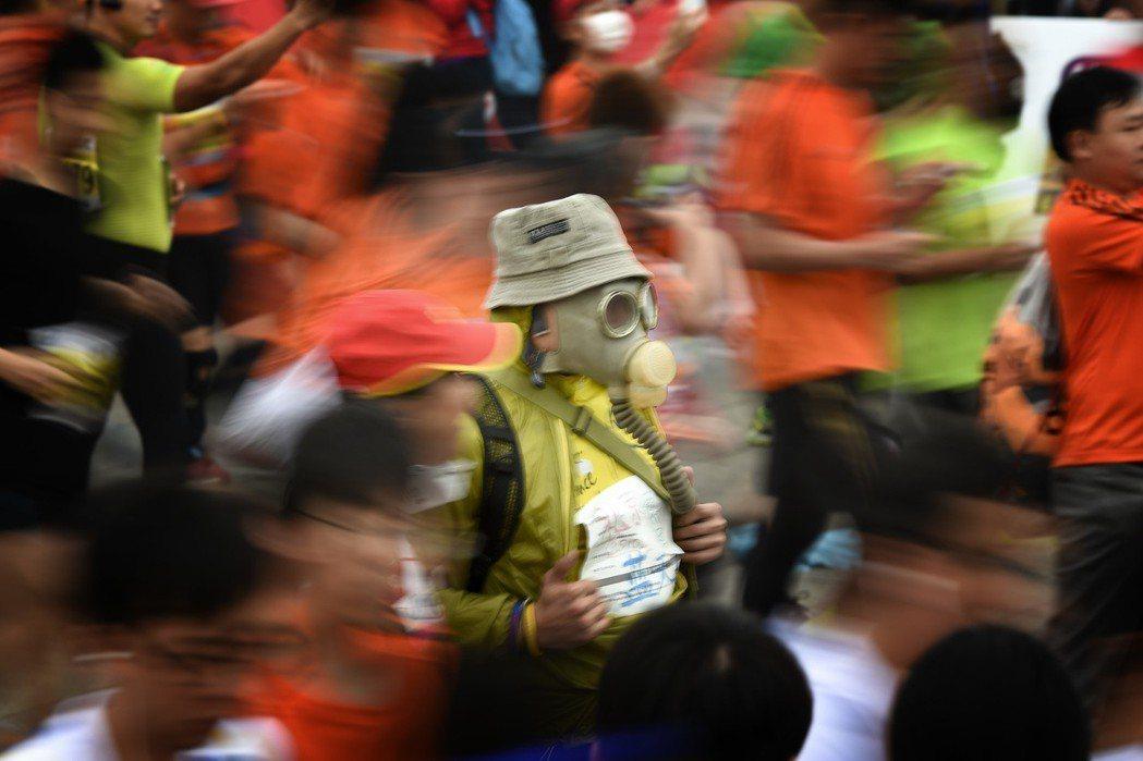2014北京馬拉松在霧霾中開賽,選手戴面具出戰。 中新社
