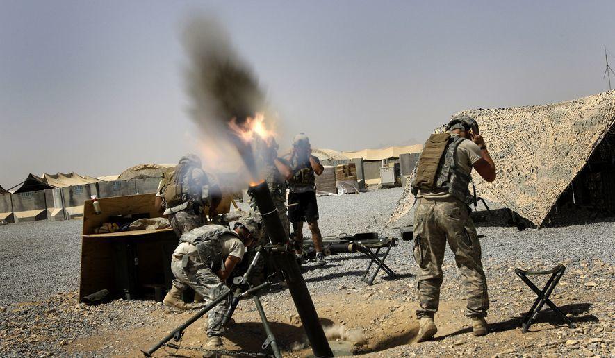 圖為在發射迫擊砲時,美軍士兵掩住耳朵保護自己的情形。 (路透)