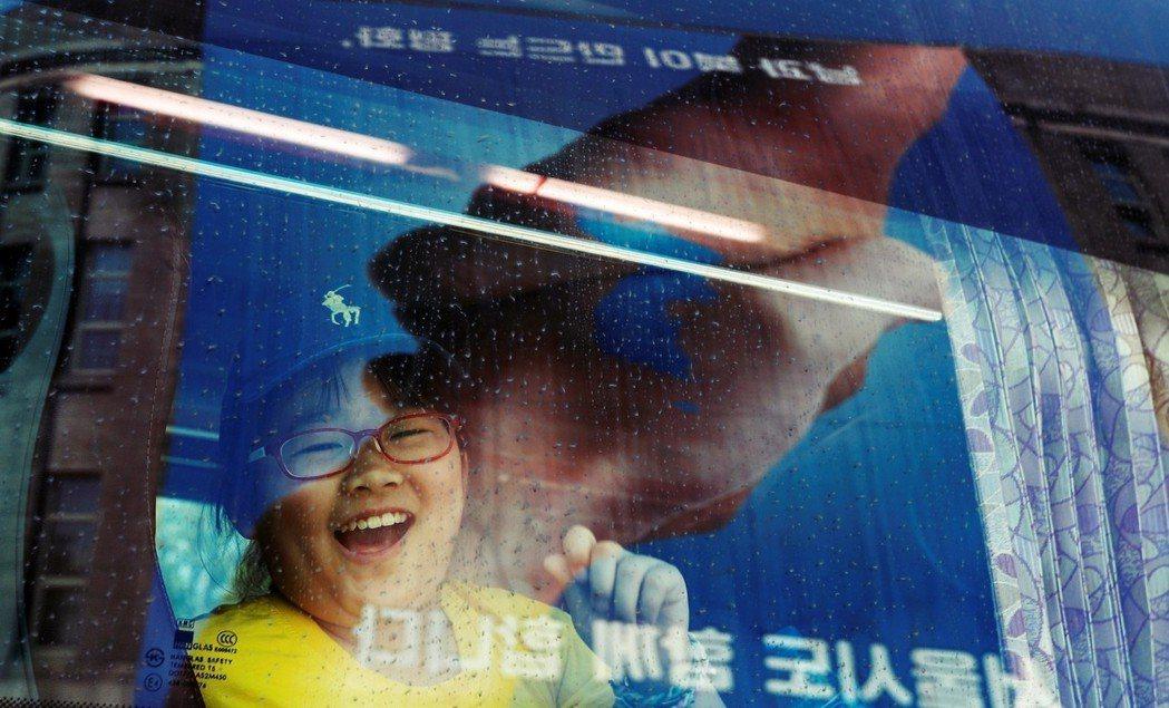 兩韓峰會前,一名小學女孩對著首爾市政廳大樓上的統一旗和平掛幅笑開了眼。 圖/路透...