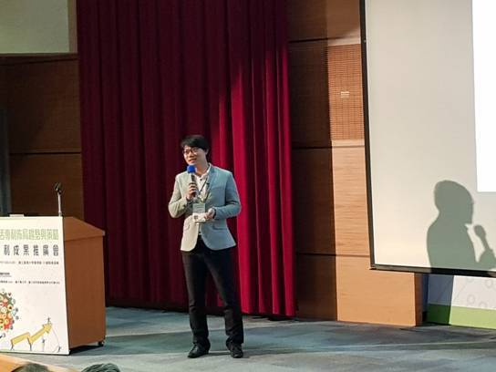 Alex Hou speaking at the conference in T...