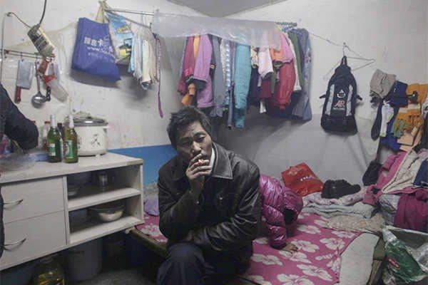 出租房內部。一名來自中國南方的北漂工人,在他約3坪大小的房內抽菸。圖片提供:達志...