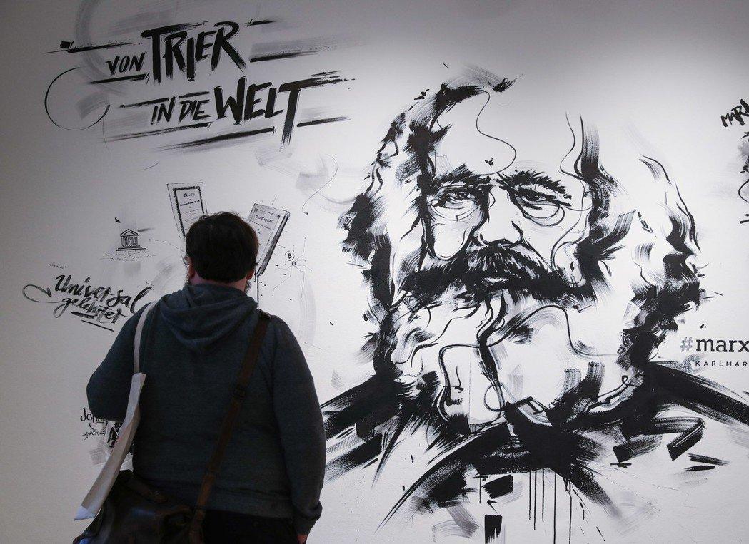 在德國特裏爾馬克思出生的故居紀念館內,一名參觀者站在一面繪有馬克思畫像的牆壁前。...
