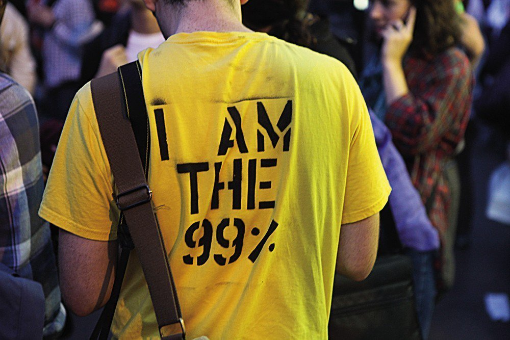 佔領華爾街運動的群眾穿著有抗議標語的T恤。