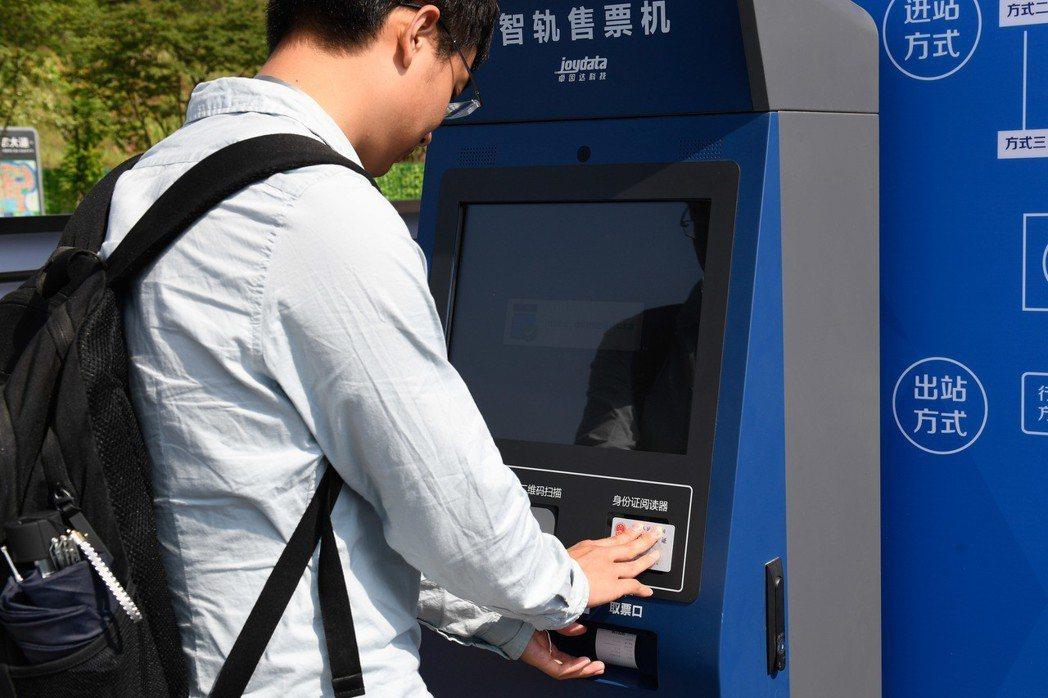 株洲市民在售票機前刷身份證取票。 新華社