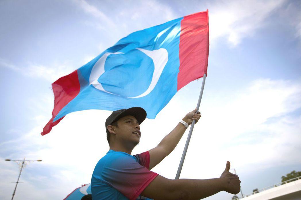 馬來西亞大選結果出爐,馬哈迪贏得執政權,年輕人在吉隆坡宮殿外揮舞希望聯盟旗幟慶祝...