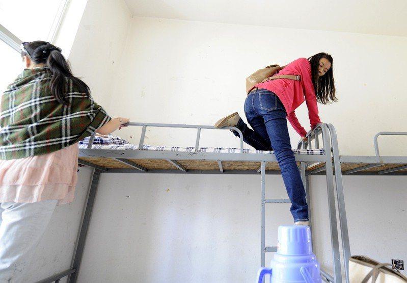中國大學生在宿舍舖床。 新華社照片