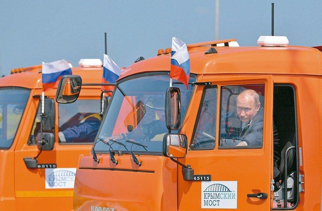 俄國總統普亭十五日坐上卡車駕駛座,準備開上克里米亞大橋完成通車典禮。 (路透)