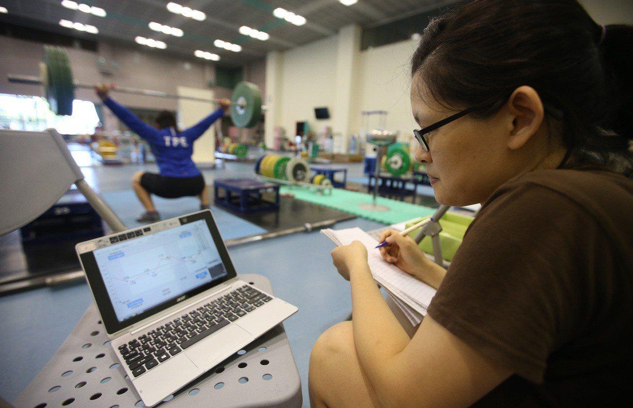 雅加達亞運女子舉重好手江念欣,練習時身上都會配戴心率偵測器,每一把舉完,一旁的電...