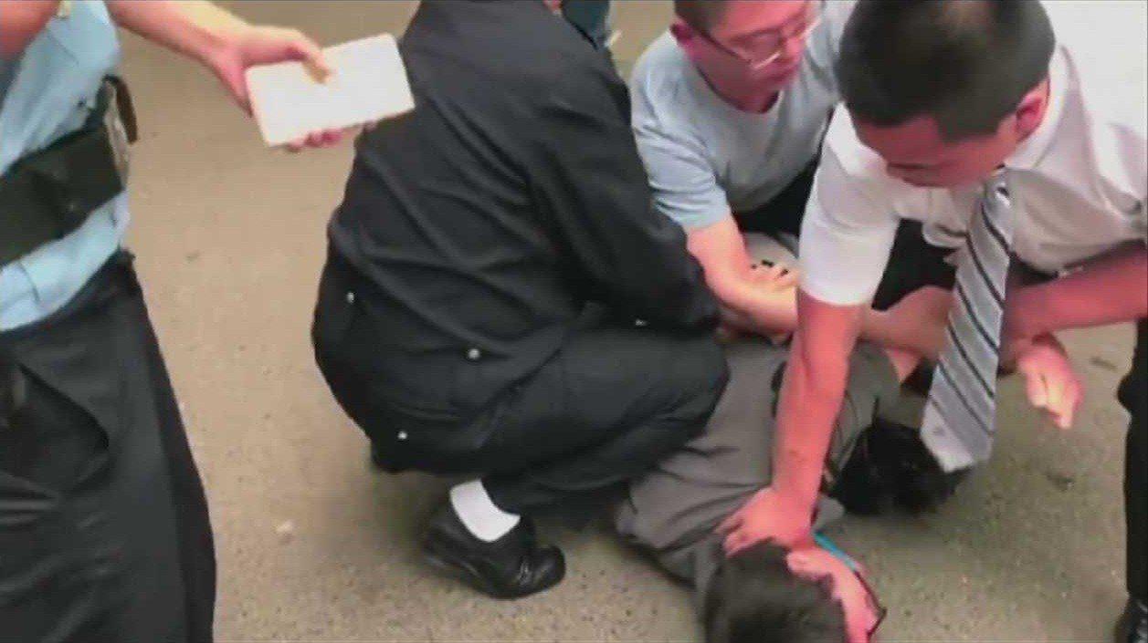 香港Now新聞攝影記者徐駿銘被北京的便衣刑警強押在地,隨後被上銬與押入警車帶走。...