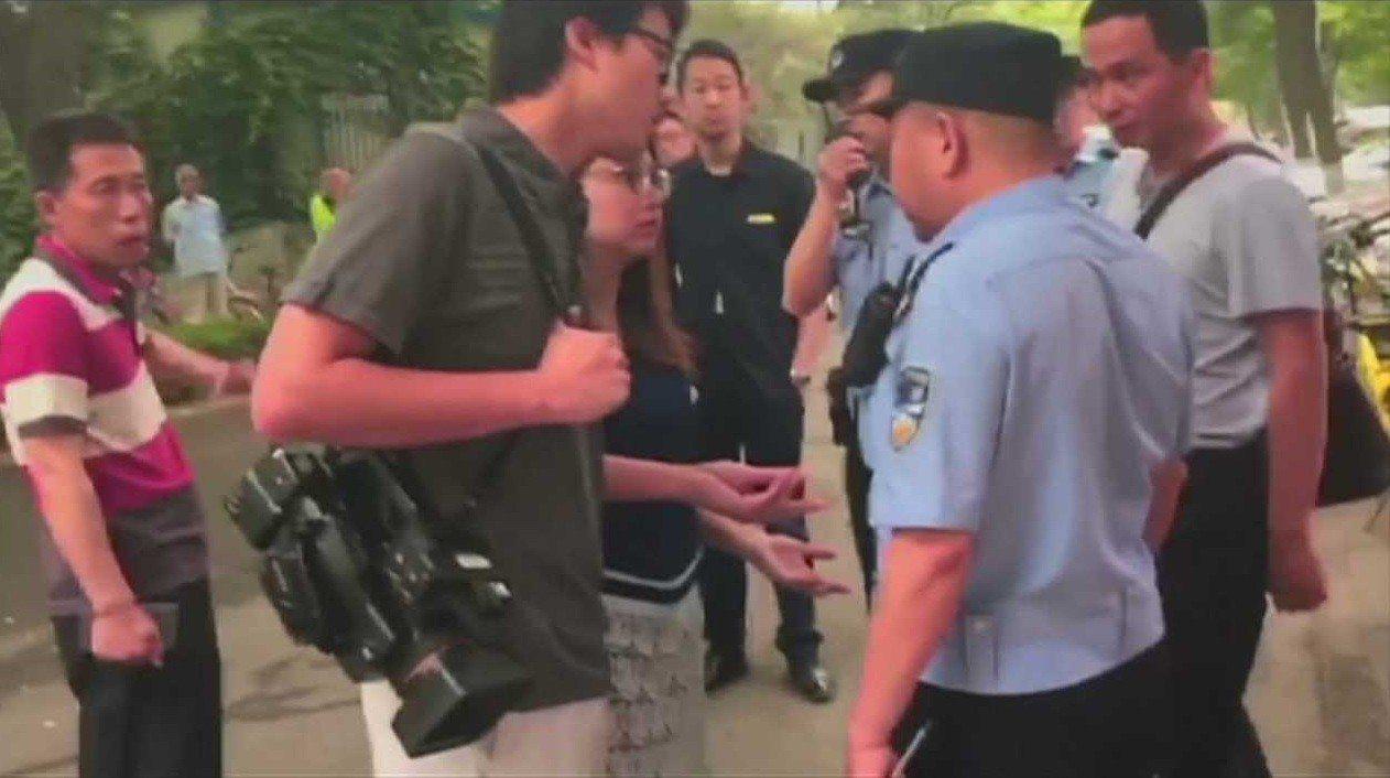 香港Now新聞攝影記者徐駿銘(左二)與記者李彤茵與警方就採訪證件被扣發生爭執。美...
