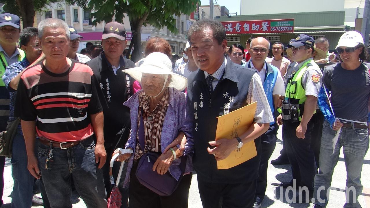 頂著烈日的抗議群眾中出現90多歲高齡阿嬤,代表會主席周聯聰趕忙扶迎上座。記者蔡維...