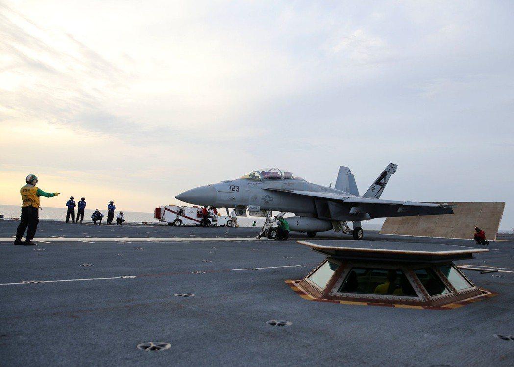 一名美軍在福特號甲板上指揮一架F/A-18F戰機進入電磁彈射系統。這套系統曾測試...