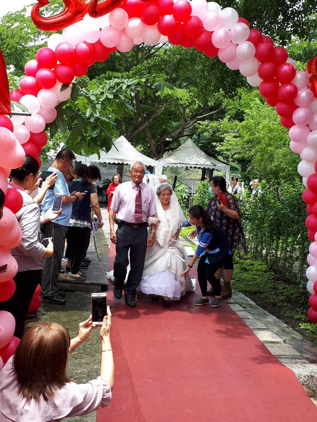 母親節來臨前,高市六龜區公所在悠然山莊舉辦慶祝活動,模範母親穿著白紗出席活動。記...